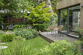 Contemporary chairs on decking by pavilion, stepping stones across lawn, table and chairs, Digitalis purpurea, Helleborus argutifolius, Libertia grandiflora, Hakonechloa macra, Acer palmatum