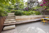 Steps leading up terraced sloping garden, built-in wooden bench, table and chairs, Pinus mugo, Euphorbia x martini, Erigeron karvinskianus, rhododendrons