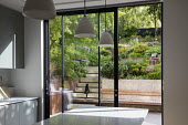 View from inside house through sliding glass doors to contemporary terraced sloping garden outside, built-in wooden bench, Pinus mugo, Euphorbia x martini, cat