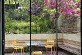 View from inside house through sliding glass doors to contemporary terraced sloping garden outside, table and chairs, built-in wooden bench, rhododendrons, alliums, Euphorbia x martini, Erigeron karvi...