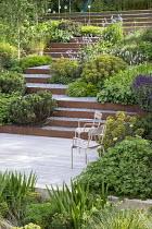 Chairs on decking, Geranium 'Rozanne', Salvia nemorosa 'Caradonna', Pinus mugo, Hakonechloa macra, Persicaria bistorta 'Superba', Euphorbia x martini, Cor-Ten steel edged gravel steps