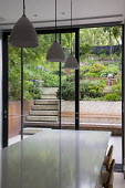 View from inside house through sliding glass doors to contemporary terraced sloping garden outside, table and chairs, built-in wooden bench, steps, Euphorbia x martini, Pinus mugo
