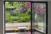 View from inside house through sliding glass doors to contemporary terraced sloping garden outside, table and chairs, built-in wooden bench, rhododendrons, alliums, Euphorbia x martini