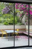 View from inside house through sliding glass doors to contemporary terraced sloping garden outside, table and chairs, built-in wooden bench, rhododendrons, Euphorbia x martini, Erigeron karvinskianus