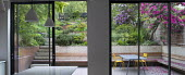 View from inside house through sliding glass doors to contemporary terraced sloping garden outside, table and chairs, built-in wooden bench, rhododendrons, Pinus mugo, Euphorbia x martini