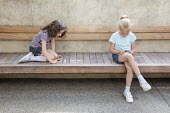 Children writing labels on built-in wooden bench