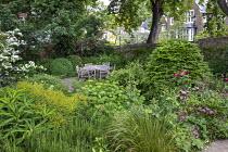 Euphorbia x pasteurii, Rosmarinus officinalis, astrantia, Hydrangea arborescens 'Annabelle', Rosa 'Munstead Wood' table and chairs on patio
