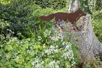 Metal fox ornament on tree stump in woodland garden, Anthriscus sylvestris