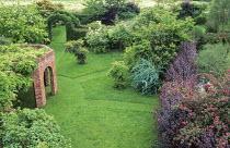 Brick arch pergola, circular lawn with mown paths through long grass, Rosa moyesii