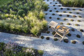 Wooden chair on gravel and stone terrace interspersed with thyme, drift of Stipa tenuissima