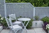 Blue painted wooden table and chairs with cushions on stone patio, trellis screen
