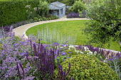Curving gravel path around lawn, salvia, nepeta, geranium, olive tree, Buxus sempervirens, blue painted summerhouse