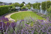 Curving gravel path around lawn, salvia, nepeta, perovskia, table and chairs