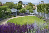 Curving gravel path around lawn, salvia, table and chairs