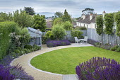 Curving gravel path around lawn, salvia, table and chairs, blue painted trellis fence