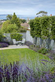Blue painted trellis fence, salvia, table and chairs on patio, view to church