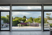 View from inside house through large windows to contemporary coastal garden outside