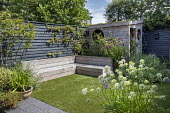 Contemporary family courtyard garden, astroturf lawn, built-in timber benches, wooden playhouse with living green roof, hidden storage, alliums in terracotta pots on black brick paving, black painted...