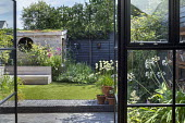 View from inside house to contemporary family courtyard garden outside, astroturf lawn, built-in timber bench, wooden playhouse with living green roof, hidden storage, alliums in terracotta pots on bl...