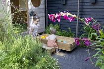 Girls playing in wooden sandpit on patio, rosemary, Verbena bonariensis