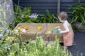 Girl playing in wooden sandpit on patio, rosemary