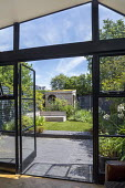 View from inside house to contemporary family courtyard garden outside, astroturf lawn, built-in timber bench, wooden playhouse with living green roof, hidden storage, black brick paving, black painte...