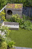 Contemporary family courtyard garden, astroturf lawn, built-in timber benches, wooden playhouse with living green roof, hidden storage, black painted fence, Verbena bonariensis
