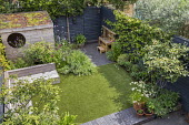 Contemporary family courtyard garden, astroturf lawn, built-in timber benches, wooden playhouse with living green roof, hidden storage, black painted fence