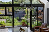 View from inside house to contemporary family courtyard garden outside, astroturf lawn, wooden playhouse with living green roof, black brick paving, black painted fence
