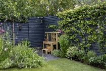Wooden play kitchen on patio, dark painted fence, penstemon, Trachelospermum jasminoides, hidden gate in dark painted fence, astroturf lawn