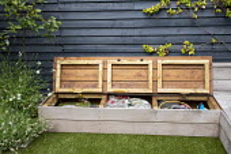 Hidden storage under built-in wooden bench, dark painted fence