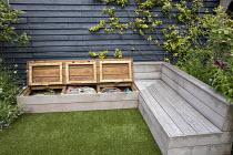 Hidden storage under built-in wooden bench, dark painted fence, astroturf lawn