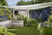 Contemporary family courtyard garden, sunsail over astroturf lawn, built-in timber benches, wooden playhouse with living green roof, hidden storage, alliums in pots, black painted fence