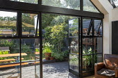 View from inside house to contemporary family courtyard garden outside, bench on black brick paving, black painted fence, log storage