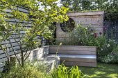 Astroturf lawn, built-in timber bench, wooden playhouse with living green roof, black painted fence, Amelanchier lamarckii, Verbena bonariensis