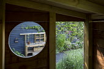 View through circular opening in wooden playhouse to play kitchen, Verbena bonariensis, Trachelospermum jasminoides climbing on dark painted fence