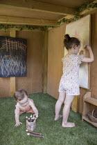Girls playing inside playhouse, astroturf carpet