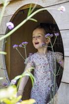 Girl playing inside playhouse, Verbena bonariensis