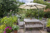 Wooden benches around table on patio, umbrella, Agastache 'Blackadder', Regal Pelargonium 'Burghi', Rosa 'Alba Maxima' and 'Sharifa Asma', Nerium oleander