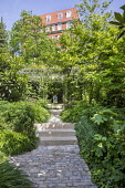 Stone path and steps leading to pool and fountain, Hakonechloa macra, magnolia, choisya, Eriobotrya japonica, hydrangea