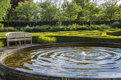 Wooden bench by circular raised pond with fountain, clipped box parterre