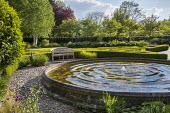 Wooden bench by circular raised pond with fountain, clipped box parterre, cobble paving
