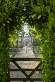 Clipped arch in laurel hedge, wooden gate, gravel path through kitchen garden, armillary sphere, cages