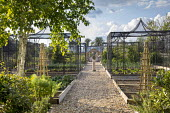 Gravel path through kitchen garden, fruit cages, armillary sphere
