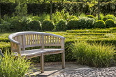 Wooden bench by clipped box parterre