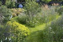 Grass path through prairie meadow, Eryngium planum, Achillea millefolium 'Summer Pastels', Stipa gigantea, Alchemilla mollis, Leaf Sphere sculpture by Paul Richardson