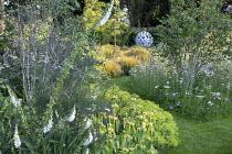 Phlomis russeliana, Alchemilla mollis, Anemanthele lessoniana, view to Leaf Sphere sculpture by Paul Richardson