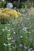 Prairie meadow, Eryngium planum, Achillea millefolium 'Summer Pastels', Stipa gigantea, Anemanthele lessoniana, Leaf Sphere sculpture by Paul Richardson