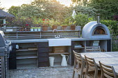 Outdoor kitchen, pizza oven, table and chairs on stone patio, sink