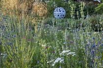 Prairie meadow, Eryngium planum, Achillea millefolium 'Summer Pastels', Stipa gigantea, Dianthus carthusianorum, Leaf Sphere sculpture by Paul Richardson